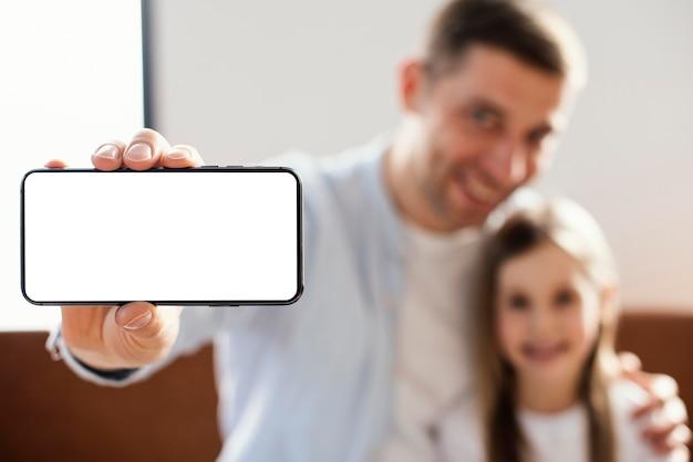Vista frontal do pai sorridente tirando uma selfie com a filha
