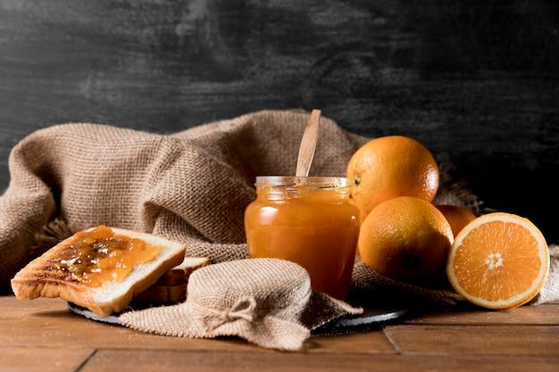 Vista frontal do pão com pote de geléia de laranja