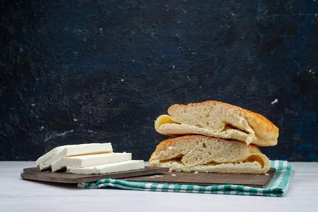 Vista frontal do pão fresco fatiado junto com queijo branco no escuro