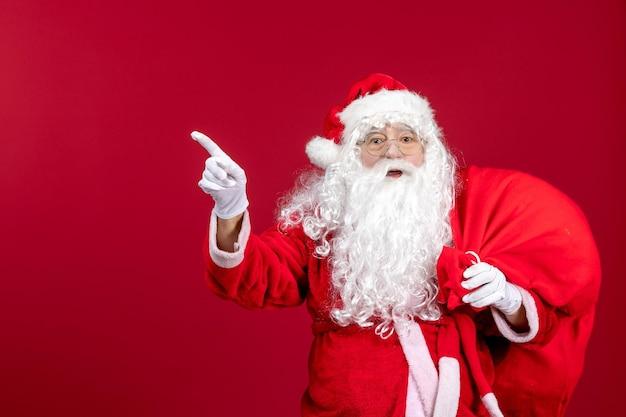 Vista frontal do papai noel carregando uma sacola cheia de presentes apontando em emoção vermelha ano novo feriado de natal