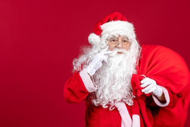 Vista frontal do papai noel carregando uma sacola cheia de presentes no feriado de natal do ano novo emoção vermelha