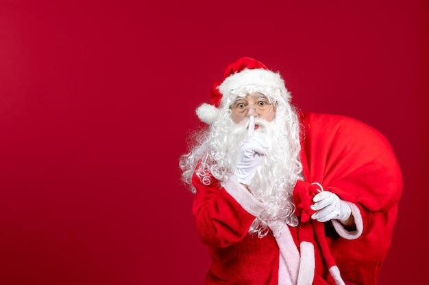 Vista frontal do papai noel carregando uma sacola cheia de presentes pedindo para guardar silêncio sobre emoção vermelha no ano novo