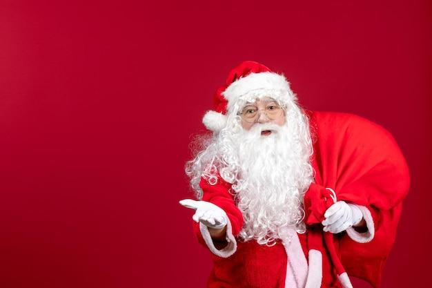 Vista frontal do papai noel carregando uma sacola vermelha cheia de presentes no feriado de natal vermelho emoção ano novo