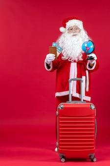 Vista frontal do papai noel com a bolsa segurando os ingressos e se preparando para a viagem na parede vermelha