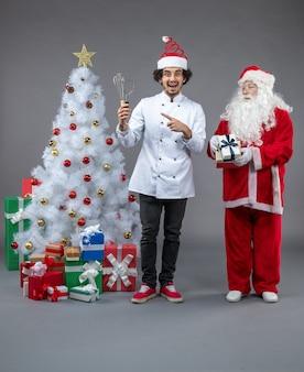 Vista frontal do papai noel com cozinheiro masculino em volta dos presentes de natal na parede cinza