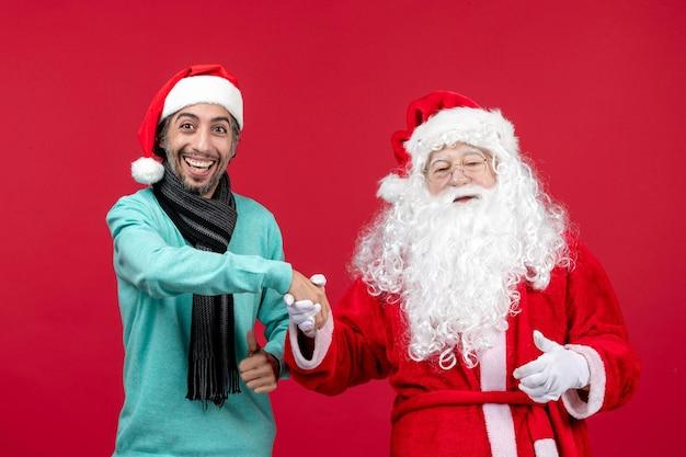 Vista frontal do papai noel com homem se sentindo feliz no vermelho presente natal emoção feriado ano novo