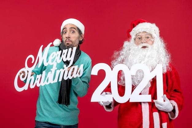 Vista frontal do papai noel com macho segurando e escritos de feliz natal no presente de natal vermelho