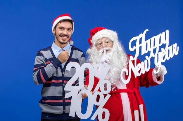 Vista frontal do papai noel com o jovem segurando feliz ano novo e os escritos de porcentagem na parede azul