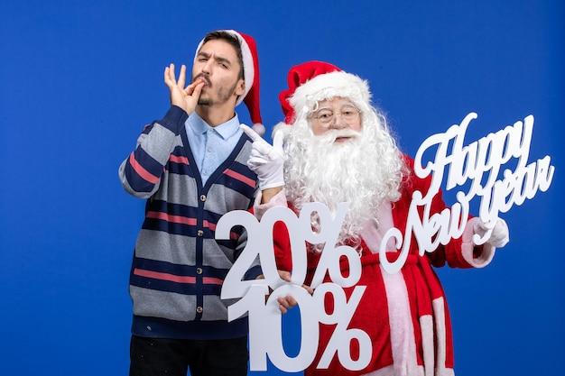 Vista frontal do papai noel com o jovem segurando os escritos de feliz ano novo e porcentagem na parede azul