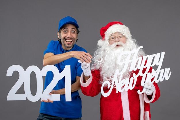 Vista frontal do papai noel com o mensageiro segurando o feliz ano novo e as pranchas de 2021 na parede cinza