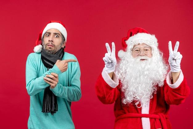 Vista frontal do papai noel com sentimento masculino animado com um presente vermelho nas férias de natal emoção ano novo