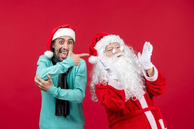 Vista frontal do papai noel com um homem em pé no feriado vermelho de natal apresentando emoção