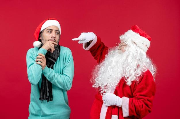 Vista frontal do papai noel com um homem em pé no vermelho presente feriado natal emoção