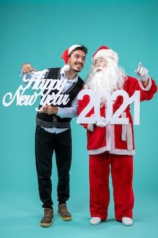 Vista frontal do papai noel com um homem segurando cartazes de feliz ano novo e 2021 na parede azul