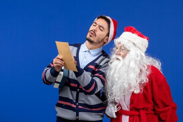 Vista frontal do papai noel com um jovem que está lendo uma carta na parede azul