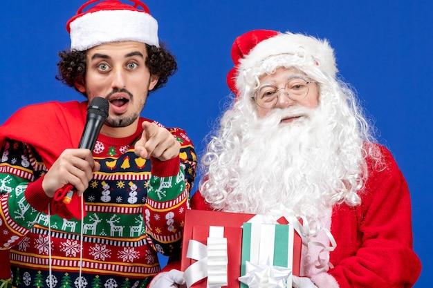 Vista frontal do papai noel com um jovem que está usando o microfone na parede azul