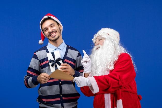 Vista frontal do papai noel com um jovem segurando uma carta e um presente na parede azul