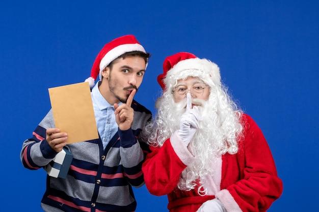 Vista frontal do papai noel com um jovem segurando uma carta na parede azul