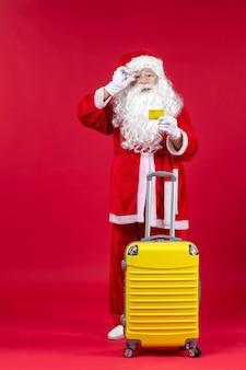 Vista frontal do papai noel com uma bolsa amarela segurando um cartão do banco amarelo na parede vermelha