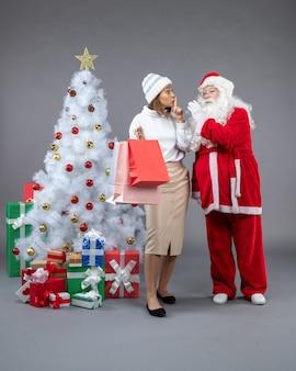Vista frontal do papai noel com uma jovem ao redor da árvore de natal e presentes na parede cinza