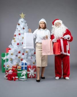 Vista frontal do papai noel com uma jovem ao redor da árvore de natal e presentes no fundo cinza