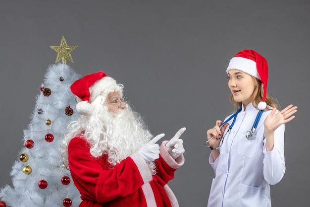 Vista frontal do papai noel com uma jovem médica na parede cinza
