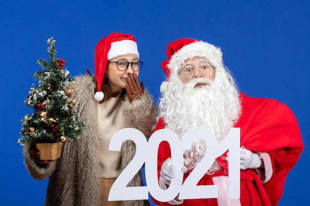 Vista frontal do papai noel com uma mulher segurando a escrita e uma pequena árvore de natal na cor azul do ano novo