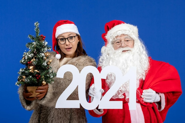 Vista frontal do papai noel com uma mulher segurando a escrita e uma pequena árvore de natal no azul do ano novo