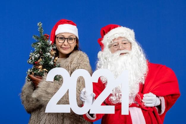 Vista frontal do papai noel com uma mulher segurando a escrita e uma pequena árvore de natal no feriado de ano novo azul
