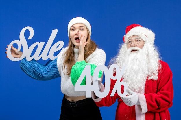 Vista frontal do papai noel com uma mulher segurando os escritos de venda na mesa azul, feriado, frio, natal, ano novo, neve