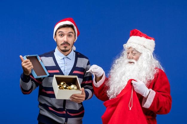 Vista frontal do papai noel dando presentes para jovens do sexo masculino em emoções de ano novo no feriado de natal azul