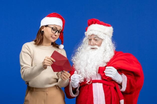 Vista frontal do papai noel e carta de abertura do jovem feminino na emoção azul, cor de ano novo de natal