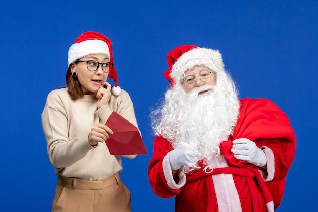 Vista frontal do papai noel e da jovem fêmea na carta de abertura em feriados azuis, natal, ano novo, cor