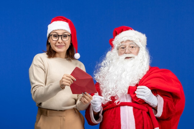 Vista frontal do papai noel e da jovem mulher na carta de abertura na cor azul do feriado de natal ano novo