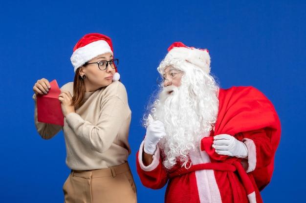 Vista frontal do papai noel e jovem fêmea carta de abertura na emoção azul do feriado natal ano novo