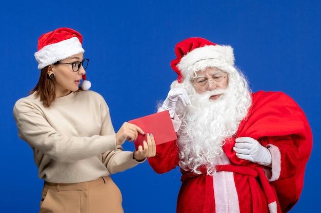 Vista frontal do papai noel e jovem fêmea carta de abertura na emoção de cor azul feriado natal ano novo