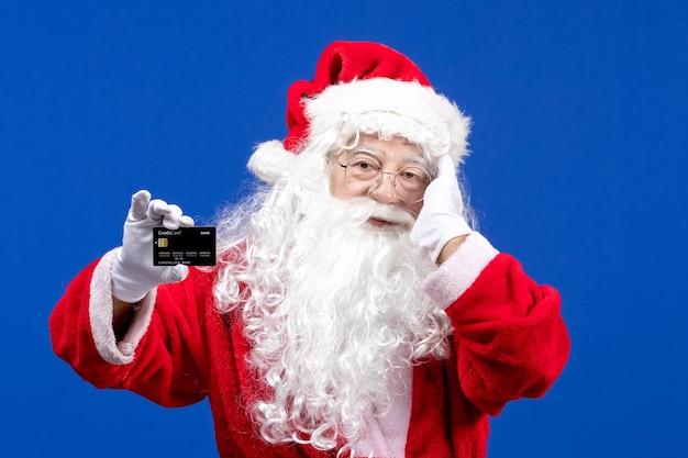 Vista frontal do papai noel em roupas vermelhas com um urso branco segurando um cartão do banco preto em um feriado de cor azul