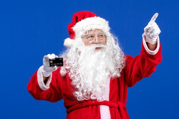 Vista frontal do papai noel em um terno vermelho segurando um cartão do banco na cor azul presente natal, feriados de ano novo