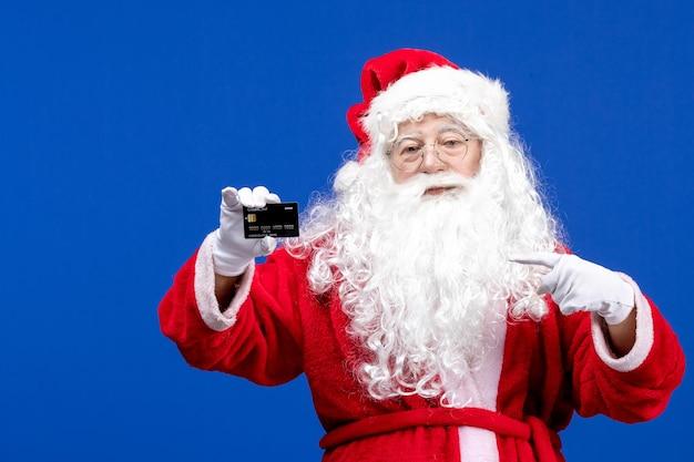 Vista frontal do papai noel em um terno vermelho segurando um cartão do banco no azul presente no feriado de natal