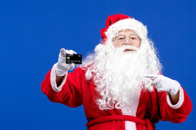Vista frontal do papai noel em um terno vermelho segurando um cartão do banco no feriado azul presente na cor do natal