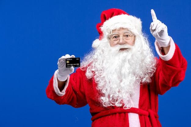 Vista frontal do papai noel em um terno vermelho segurando um cartão do banco no feriado azul presente
