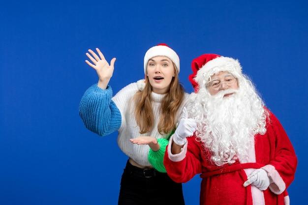 Vista frontal do papai noel junto com a jovem fêmea em pé na cor azul do feriado de ano novo e emoções de natal