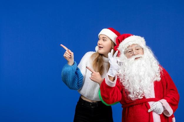 Vista frontal do papai noel junto com a jovem fêmea em pé na cor azul do feriado do ano novo natal emoção
