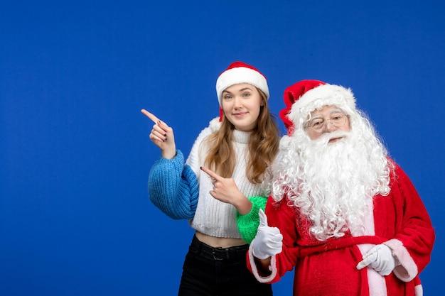 Vista frontal do papai noel junto com a jovem fêmea em pé na cor azul do feriado do ano novo natal
