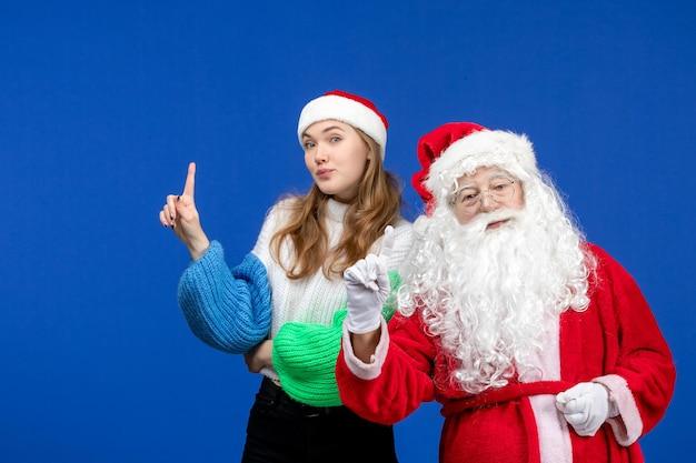 Vista frontal do papai noel junto com a jovem fêmea em pé na mesa azul, ano novo, feriado, natal
