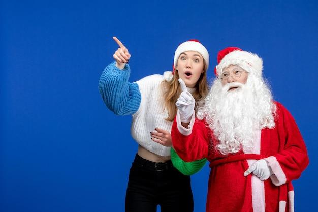 Vista frontal do papai noel junto com a jovem fêmea em pé no modelo azul do ano novo.