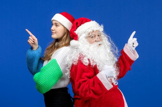 Vista frontal do papai noel junto com a jovem fêmea nas emoções de ano novo azul feriado humano cor de natal
