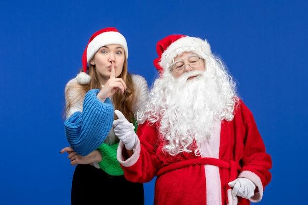 Vista frontal do papai noel junto com a jovem fêmea no feriado azul humano cor do natal ano novo emoção