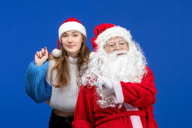 Vista frontal do papai noel junto com a jovem fêmea no feriado de ano novo azul humano com cores de natal