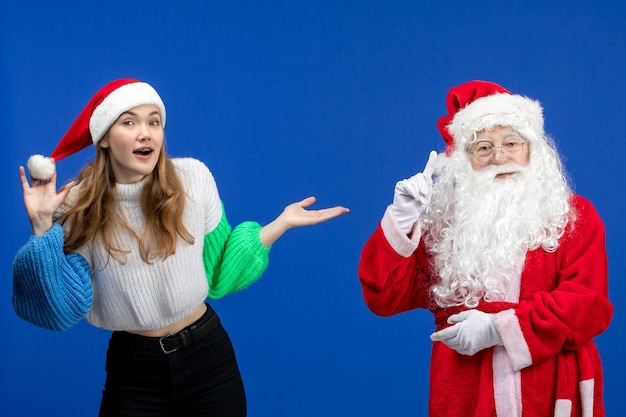 Vista frontal do papai noel junto com uma jovem fêmea em pé no modelo azul do feriado de ano novo.